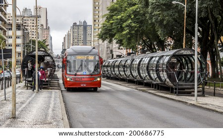 CURITIBA, BRAZIL - MARCH 30: Curitiba's public transportation system in Curitiba, PR, Brazil with its tube-shapped bus stops and red buses loading and unloading passengers on March 30, 2014. - stock photo