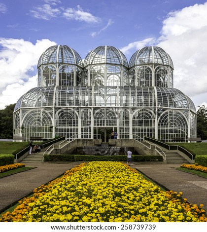 CURITIBA, BRAZIL - MARCH 10, 204: View of Curitiba in Parana, Brazil showcasing the architecture of the Green House at Curitiba Botanic Garden on summer day with locals passing by on March 10, 2014. - stock photo