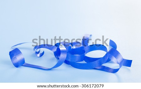 Curled blue holiday ribbon on a blue background - stock photo
