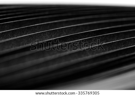 curled in a roll black paper ribbon. Macro lens closeup shot 1:1 - stock photo