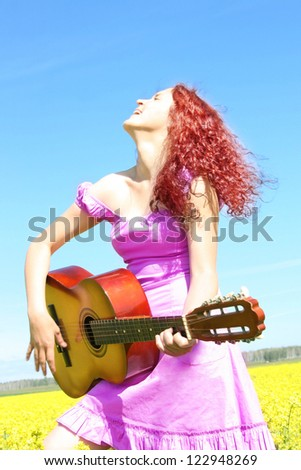 curled redhead woman in a purple summer dress in rapeseed field - stock photo