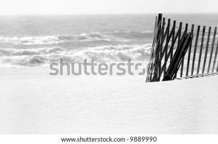 Curled sand dune fence on pristine beach with ocean in distance - stock photo