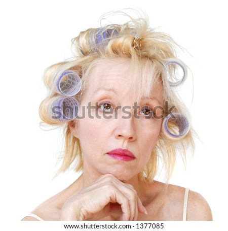 Curler Woman. A blonde woman with lavender curlers in her hair, with an expression of hoping she'll look better later.  Bad hair day. - stock photo