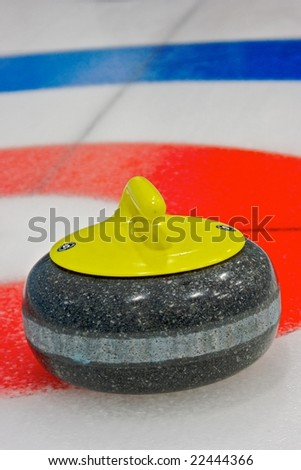 Curling rock sits near the button during a league game