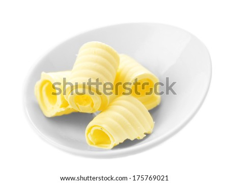 Curls of fresh butter in bowl, isolated on white