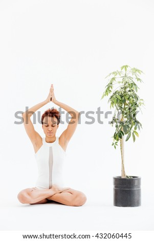 Curly african american young woman practicing lotus yoga pose near small tree in pot over white background - stock photo