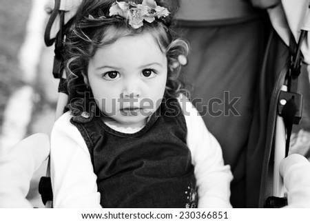 curly baby girl  in stroller - stock photo