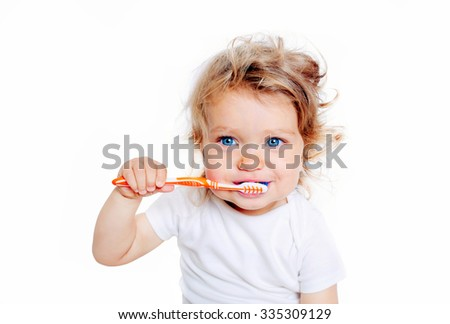 Curly baby toddler brushing teeth. Isolated on white background. - stock photo