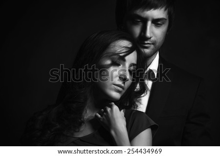 Curly brunette girl and handsome guy in a suit perfect romantic couple. Black and white portrait - stock photo