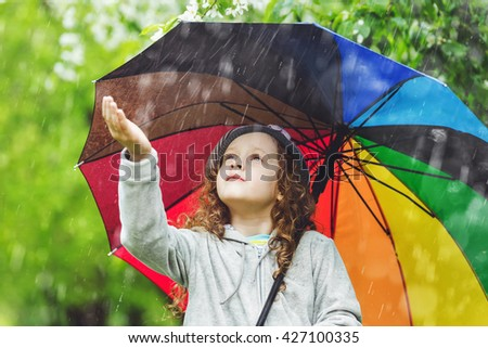 Curly child enjoy to spring rain outdoors. - stock photo