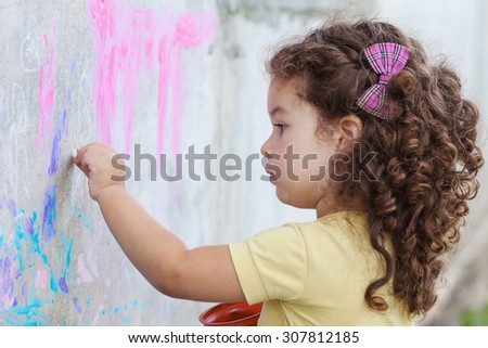 Curly cute baby girl drawing with chalk on the wall - stock photo