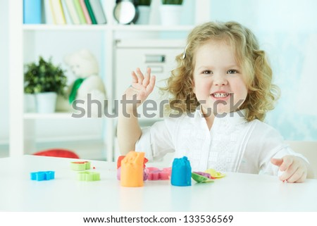 Curly cutie having fun playing with clay at nursery - stock photo