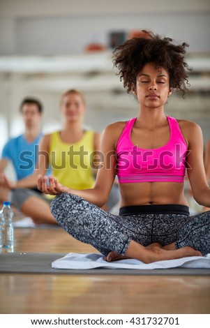 Curly female in lotus pose meditate in fitness class - stock photo