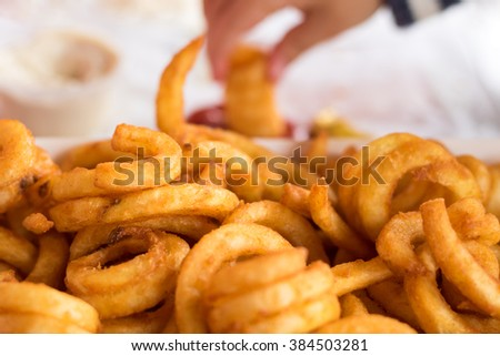 Curly fries with hand dipping in ketchup - stock photo