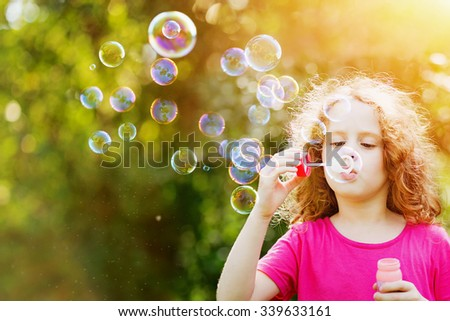 Curly girl blowing soap bubbles in summer park.