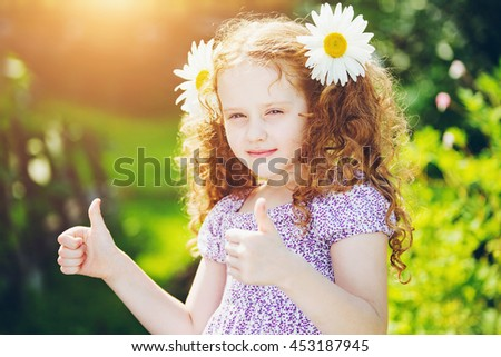Curly girl with daisy in her hairs, showing thumbs up. - stock photo