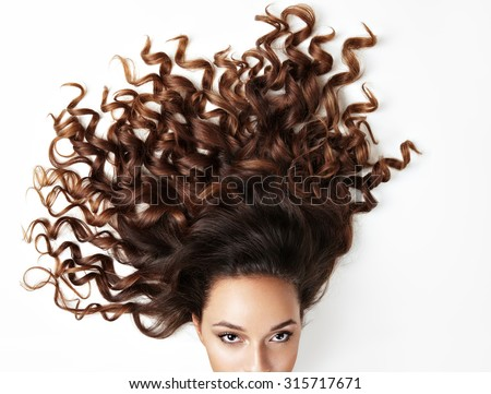curly hair and part of woman'?s face, looking at the camera - stock photo