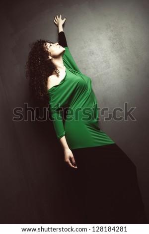 curly hair beautiful young woman in elegant green dress studio shot - stock photo