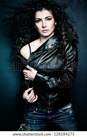 curly hair beautiful young woman wearing black leather jacket and blue jeans, studio shot