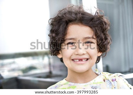 Curly hair Kid with lost teeth with toned color and selective focus