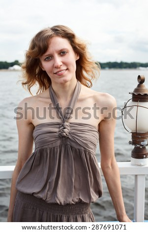 Curly hair woman in dress standing at the ship deck and looking at camera