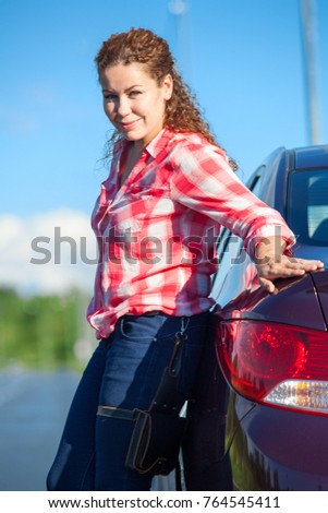 Curly hair woman in red and white shirt leaning her car while standing roadside