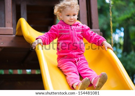 Curly haired blonde girl sliding at playground - stock photo