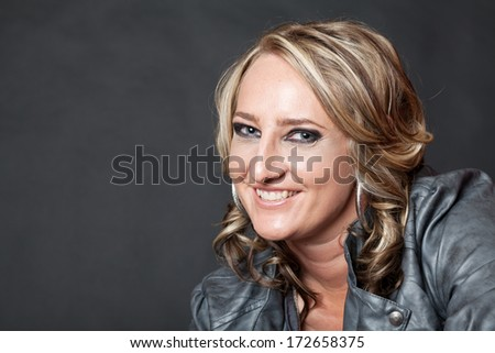 Curly haired blonde woman wearing fake leather jacket in studio against grey background - stock photo