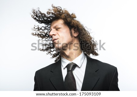 Curly haired business man moving head with hair in the air - stock photo