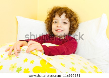 Curly haired girl laying in bed and smiling. - stock photo