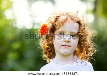 curly-haired little girl with a flower in her hair - stock photo