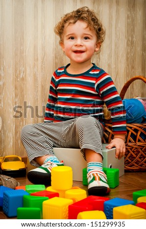 curly little boy playing with blocks on the floor - stock photo