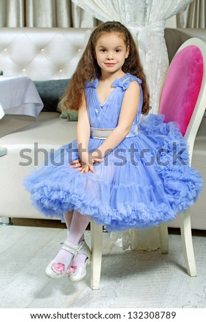 Curly little girl in blue dress sitting on the chair - stock photo