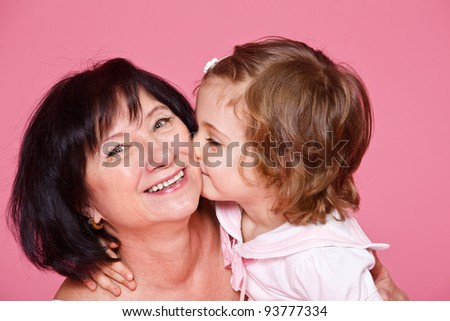 Curly little girl kissing grandmother