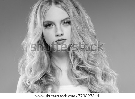 Curly long hair blonde young model. Beauty girl with curly perfect hairstyle black and white monochrome