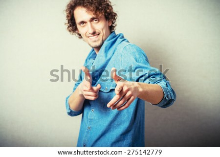 Curly man index finger at the camera. On a gray background. - stock photo