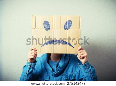 Curly man with a kraft cardboard instead of a head, a sad smiley. On a gray background. - stock photo