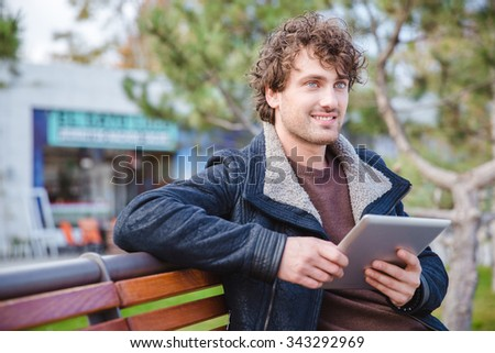 Curly positive handsome young guy on black jacket using tablet on the wooden bench in park and looking away - stock photo