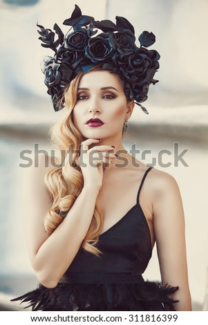 Curly sensual blonde with a wreath of black flowers