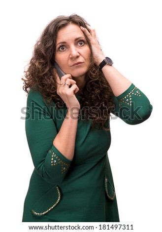 Curly shocked brunette talking on a phone on a white background - stock photo