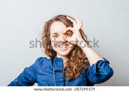 Curly smiling woman looking through her fingers, a gesture okay. Gray background. - stock photo