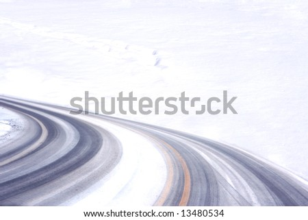 Curly tired tracks fading into snowfield for winter background - stock photo