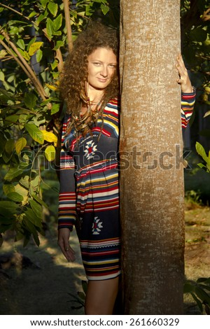 curly woman posing beside a tree trunk - stock photo