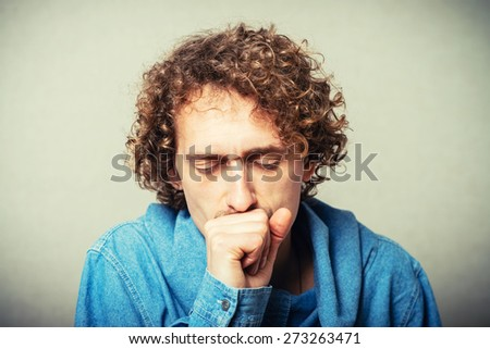 Curly young man coughs with hand near mouth. On a gray background - stock photo