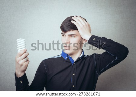 Curly young man talking on the phone, receiving bad news. On a gray background - stock photo
