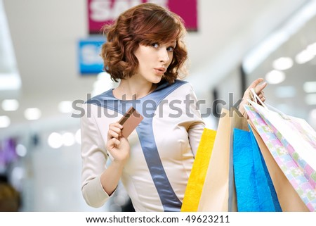Curly young woman in shop with a credit card - stock photo