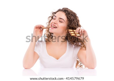 Curly young woman with plate of  milk chocolate at table. Concept of diet. - stock photo