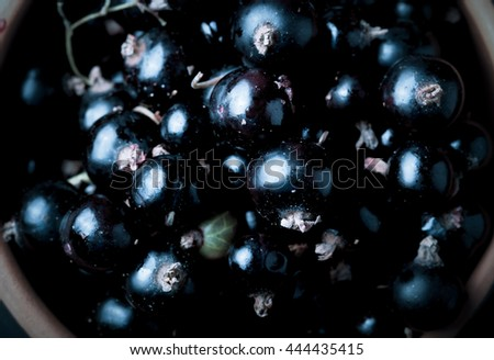 Currant berries in a clay bowl. Selective focus. Shallow depth of field. Toned.