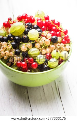 Currants and gooseberry in a bowl on the table - stock photo