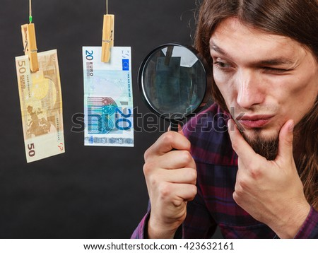 Currency exchange concept. Man worker check verify money cash. Payment hang on laundry line. Guy with loupe. - stock photo